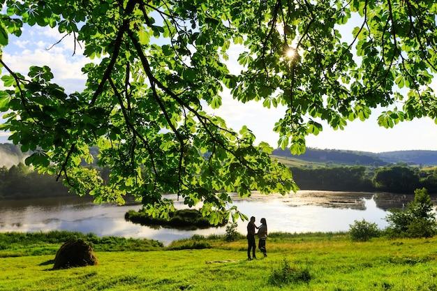 水辺の公園で妊婦と夫が散歩し、美しい自然と空に抱き合う