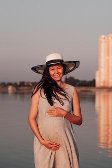 日没時の妊婦は、麦わら帽子と灰色のドレスを着た幸せな笑顔の妊婦が彼女を抱きしめています...