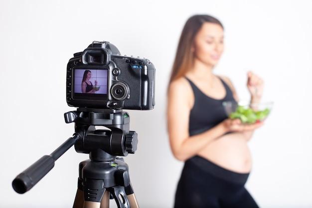 妊娠中の女性ブロガーは、妊娠中の適切な栄養についてカメラにビデオを録画します