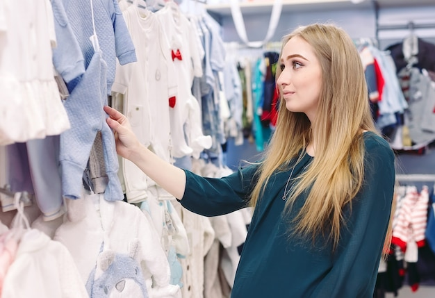 Беременная женщина выбирает детскую одежду в магазине.