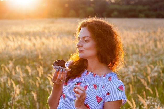 晴れた日に小さなケーキを味わう美しいドレスを着た妊婦。自然の中で妊娠中の家族の写真撮影
