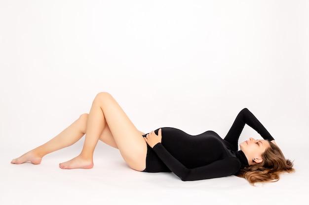 검은 bodysuit에서 임신 한 여자 거짓말