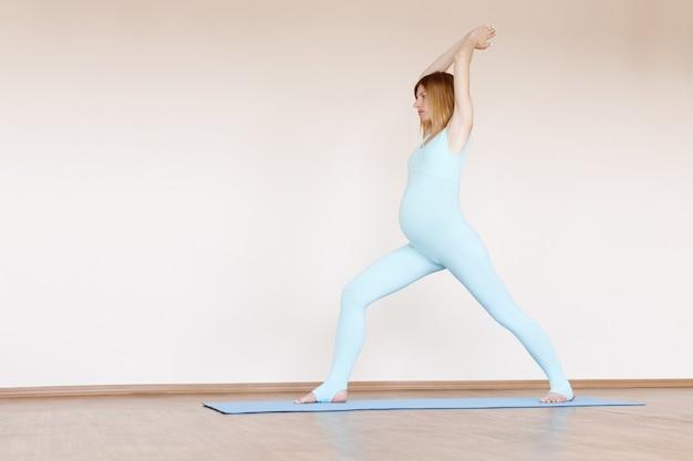 青いジャンプスーツを着た妊婦は、明るい背景で充電に従事しています。妊娠中の女性のための体操