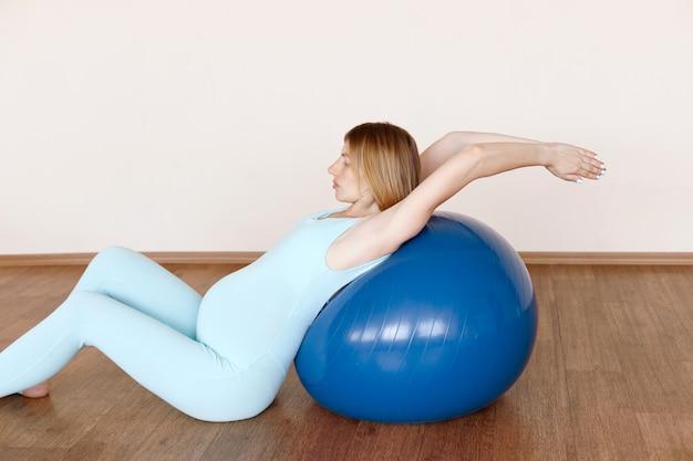 青いジャンプスーツを着た妊婦が、ヨガスタジオのフィットネスボールでストレッチします。妊娠中の女性のためのヨガ