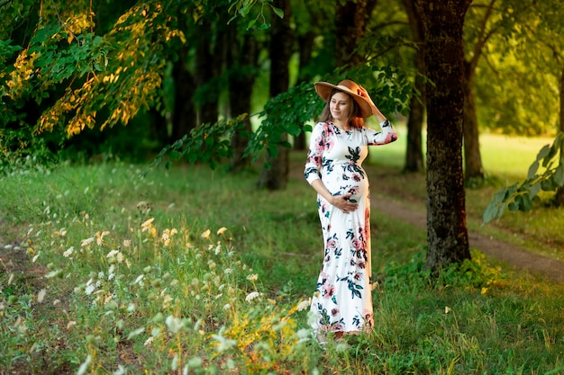 ドレスと帽子をかぶった妊婦が夏に森の中を歩く、妊婦が自然の中を歩く