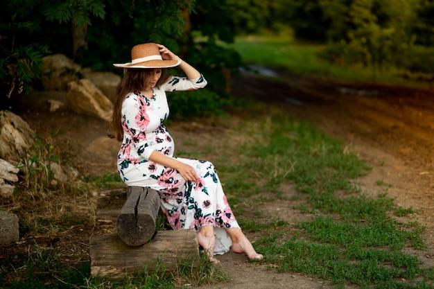 드레스를 입은 임산부는 여름에 숲에서 자연을 산책합니다.