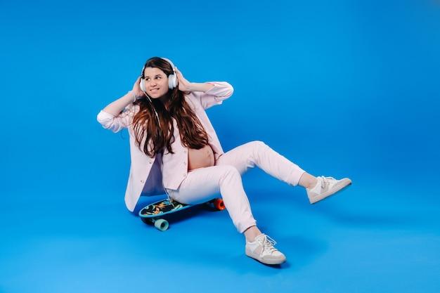 ピンクのスーツを着た妊婦がヘッドフォンでスケートボードに座って、青い背景で音楽を聴きます。