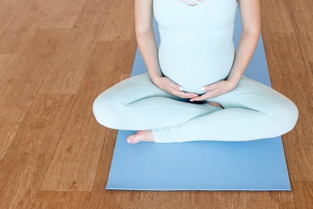 スポーツジャンプスーツを着た妊婦は、スポーツマットの上でお腹を抱きしめます。妊娠中の女性のためのヨガ。閉じる