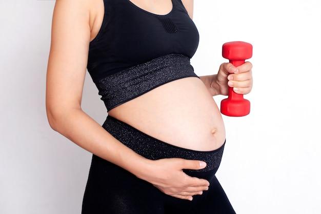 Беременная женщина в спортивной форме держит в руке гантель