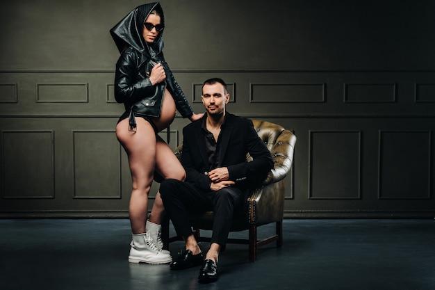 Беременная женщина в черной одежде и платке и мужчина в костюме в студии на темном фоне