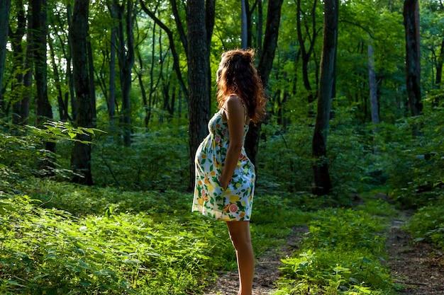晴れた日に緑の森の小道に美しい色のドレスを着た妊婦が立っています。自然の中で妊娠中の家族の写真撮影