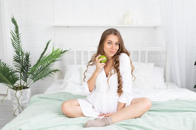 임신한 여성은 집에 있는 침대에서 녹색 사과를 먹고 배를 만지는 젊은 행복한 임산부입니다. 모성, 임신, 복사 공간의 개념
