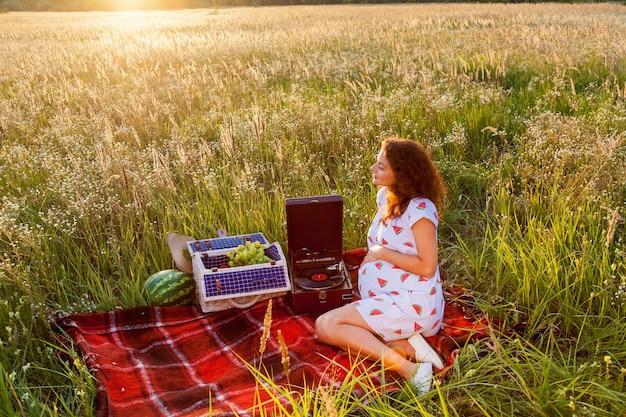 晴れた日には、蓄音機の近くの赤い毛布と麦畑の果物の入ったバスケットに妊婦が座っています。
