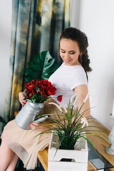 妊娠中の女性が赤い花に水をまき、テーブルに座っています。腹がかわいい妊娠