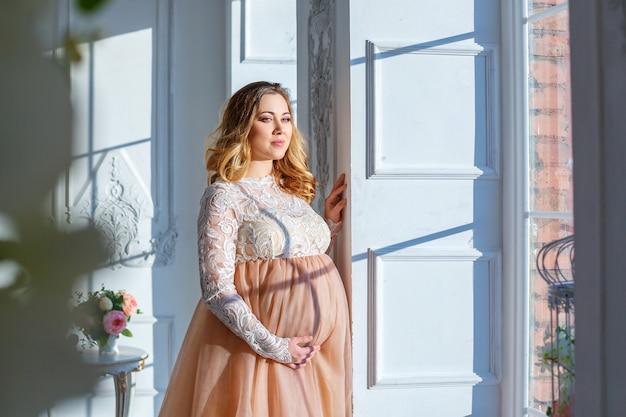 美しいドレス、出産の窓の近くの妊娠中の女性