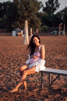 ピンクの水着と白で魅力的な脚の長い妊婦を笑顔のビーチで妊婦...