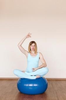 妊娠中の女性がヨガのアーサナでフィットネスボールに座っています。バランスヨガ。
