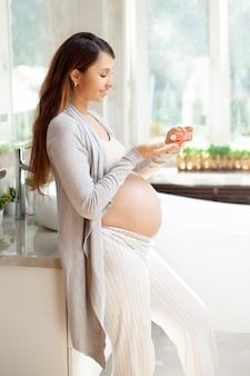 妊娠中の女性がストレッチマークからのクリームで彼女の胃を塗ります