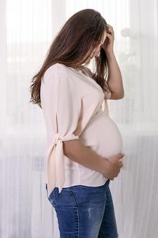 妊娠中の女性が窓際に立ち、お腹を撫でる