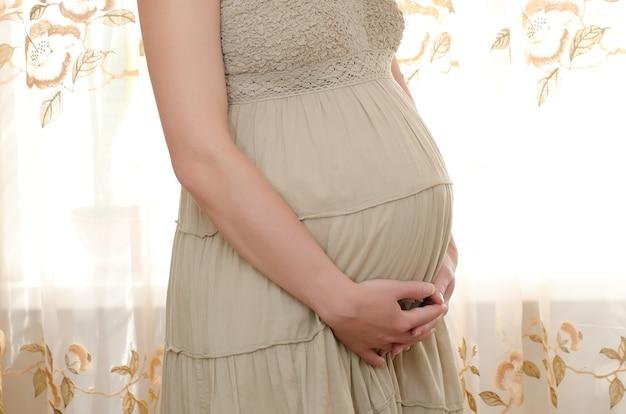 赤ちゃんを待っている妊婦がおなかを優しく抱きしめます