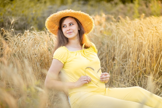 Беременная женщина гуляет по пшеничному полю летом
