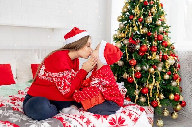 빨간 스웨터와 모자를 쓴 아기를 안고 있는 임산부는 크리스마스 트리 아래에서 선물을 주고 집에서 침대에서 서로 축하하는 키스를 하고 새해와 크리스마스를 기뻐합니다