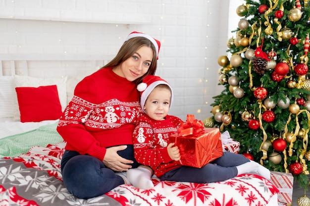 빨간 스웨터와 모자를 쓴 아기를 안고 있는 임산부는 집에서 침대에 있는 크리스마스 트리 아래에서 선물을 주고 새해와 크리스마스를 기뻐합니다