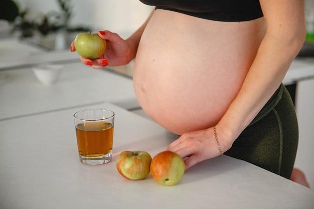 Возле стола стоит беременная с голым животом с яблоком в руках. рядом стакан яблочного сока