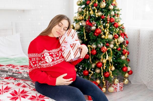 집에 있는 크리스마스 트리 아래 빨간 스웨터를 입은 임산부가 큰 배를 쓰다듬고 아기를 꿈꾸며 새해와 크리스마스를 즐기고 있다