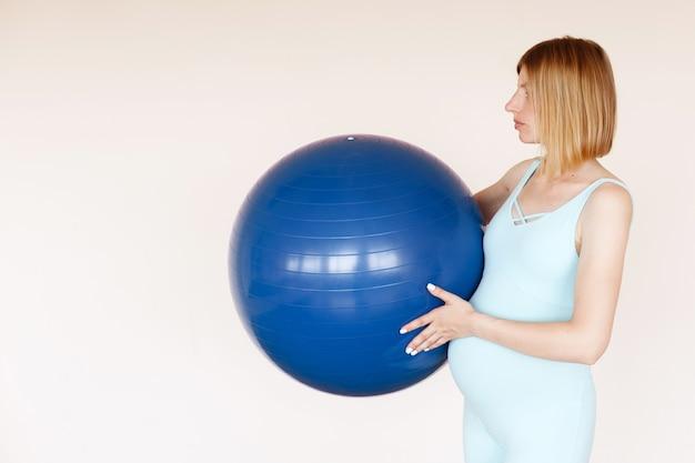 明るい背景に彼女の袖にスポーツボールを持つ妊婦。妊娠中の女性のためのヨガ