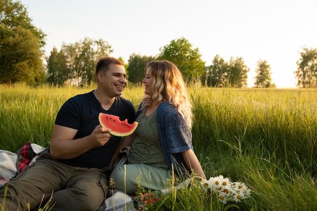 Беременная женщина с мужем на фоне поля