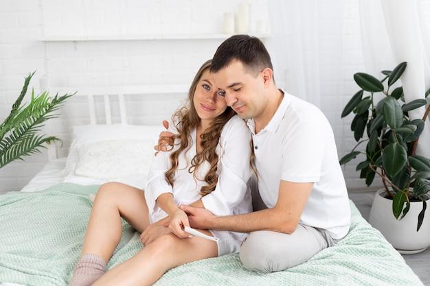 남편이나 미래의 부모인 엄마 아빠와 함께 있는 임산부가 초음파 사진을 보고 집에 있는 침대에서 배를 쓰다듬고 있다. 모성, 임신, 행복한 가족의 개념