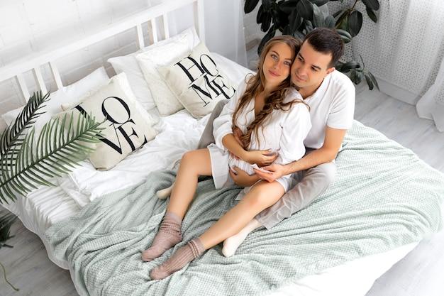 남편이나 미래의 부모 엄마와 아빠가 있는 임산부는 집에 있는 침대에서 배를 쓰다듬습니다. 모성, 임신, 행복한 가족의 개념