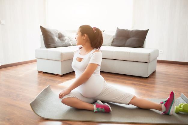 임신 한 여자는 집에서 요가 매트에 운동을합니다. 임신과 스포츠. 임산부를위한 오가와 필라테스. 임신 3 기.