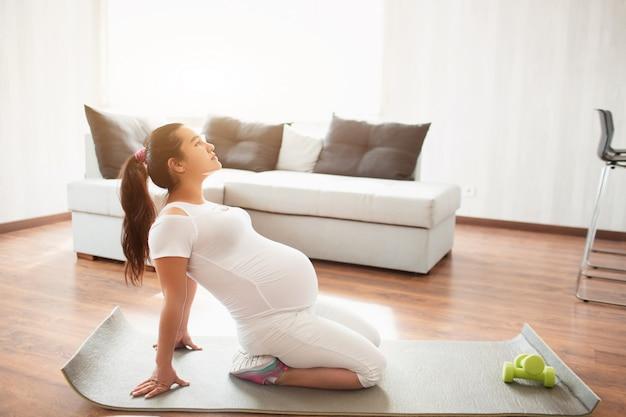 임신 한 여자는 집에서 요가 매트에 밖으로 작동합니다. 임신과 스포츠. 임산부 yyoga 및 필라테스. 임신 3 기