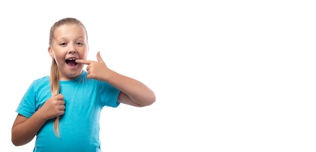 青いtシャツを着た未就学児の女の子は、白い背景に彼女の歯に指を示しています。乳歯が抜け落ち、口を開けると永久歯が生えてきます。口腔衛生の概念