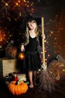 호박을 손에 들고 마녀 모자를 쓴 미취학 아동이 손전등 기둥이 달린 빗자루...