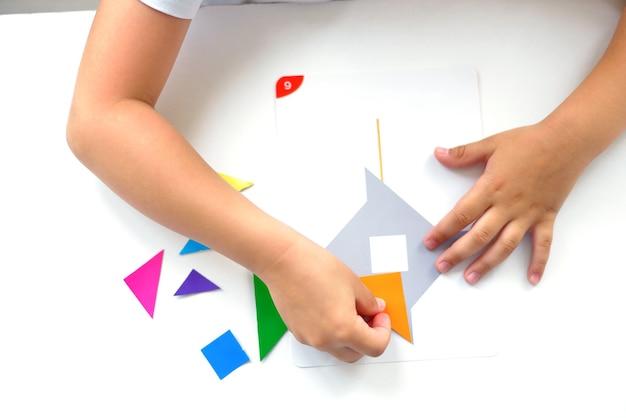 탁자에 앉아 있는 미취학 아동은 기하학적 도형에서 그림을 수집합니다. 몬테소리의 유아기 발달 개념. 논리와 상상력의 게임.