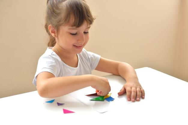 テーブルに座っている未就学児の女の子は、幾何学的図形から図面を収集します。モンテッソーリによる幼児発達の概念。論理と想像力のゲーム。
