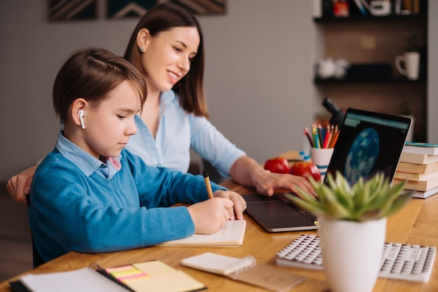 Мальчик предподросткового возраста использует ноутбук для видеозвонка со своим учителем рядом с матерью.