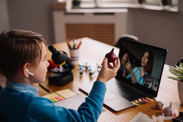 노트북을 사용하여 선생님과 화상 통화를하는 10 대 초반 소년