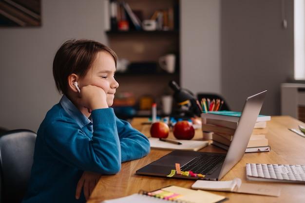 プレティーンの少年がラップトップを使用してオンラインクラスを作成する