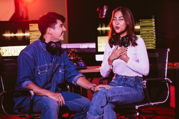 かなりアジアの女性がリハーサルセッションでスタジオでプロデューサーと一緒に歌おうとします。音楽業界でのパフォーマンスとショー。コピースペースのある画像。小規模で家庭的なレコーディングスタジオ。