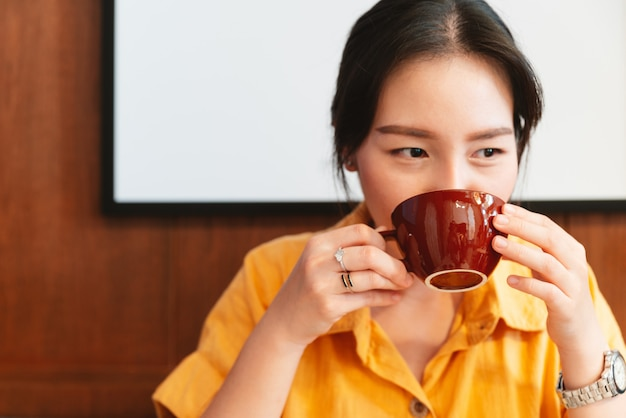 黄色のシャツを着たかなりアジアの女性が幸せな目でカフェでコーヒーを飲んでいます。