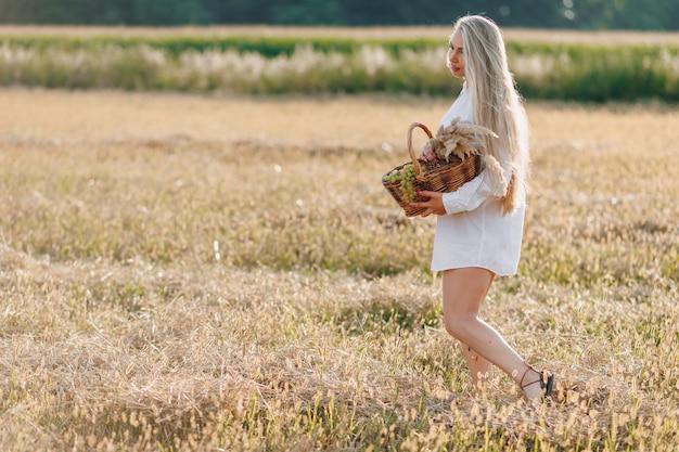 日没時のフィールドで長い髪のかわいい金髪の女性は、フルーツバスケットとストローの花束を運ぶ。夏、農業、自然、田舎の新鮮な空気。