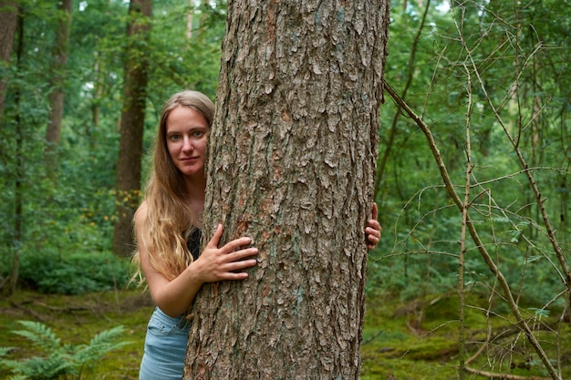 長い髪のかなり金髪の白人女性が森の木の幹の後ろに隠れています
