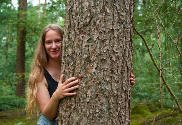 長い髪のかなり金髪の白人女性が笑顔で森の木の幹を抱いています