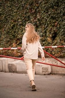 かなり金髪の若い女性が通りを歩いていて、彼女はジーンズとベージュのシャツを着ています。カジュアルな装いで笑顔で散歩する美少女