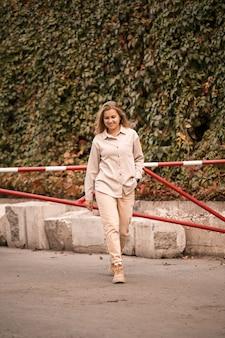 かなり金髪の若い女性が通りを歩いていて、彼女はジーンズとベージュのシャツを着ています。散歩のために彼女の顔に笑顔でカジュアルなスタイルに身を包んだ美しい少女
