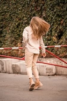 예쁜 금발의 젊은 여성이 거리를 걷고 있으며 청바지와 베이지색 셔츠를 입고 있습니다. 산책을 위해 얼굴에 미소를 띠고 캐주얼한 옷을 입은 아름다운 소녀